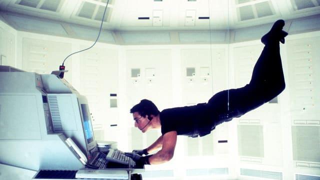 Ein Mann hängt kopfüber an einem Seil und bedient einen Computer.