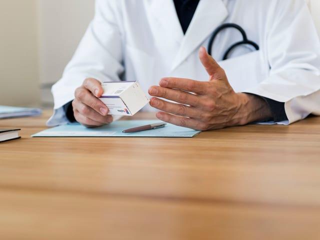 Ein Arzt im weissen Kittel hält ein Medikament in den Händen und gestikuliert. Er sitzt an einem Tisch.
