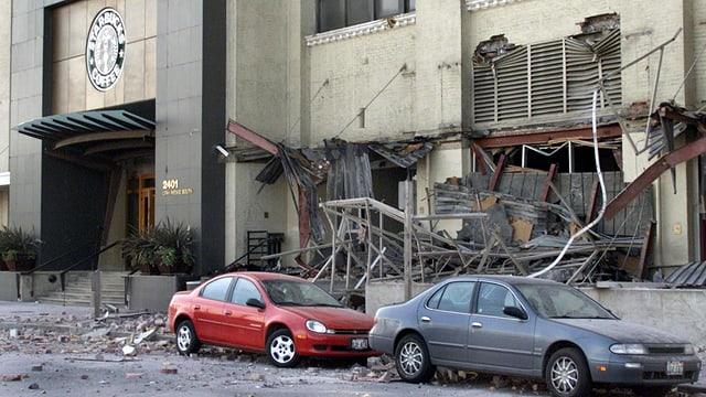 Trümmer an Autos die vor einem Haus stehen.