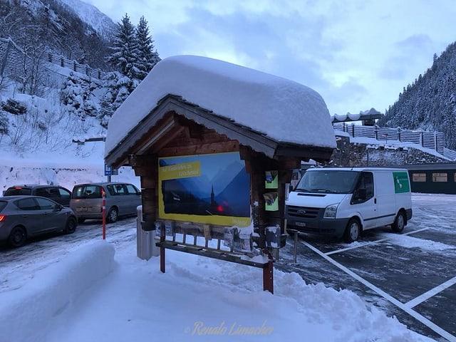 Eine Infotafel im tiefen Schnee.