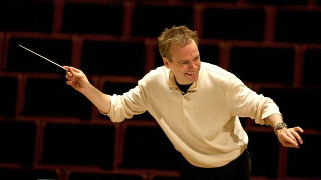 Der Dirigent Jonathan Nott – kurze blonde Haare, heller Pullover – in Bewegung.