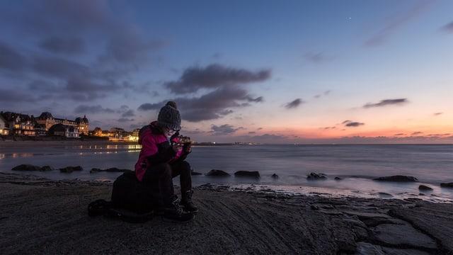Frau sitzt in der Dämmerung auf einem Stein am Strand und schaut aufs Smartphone.