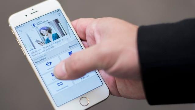 Eine Hand hält ein Smartphone und bedient eine App der ZKB