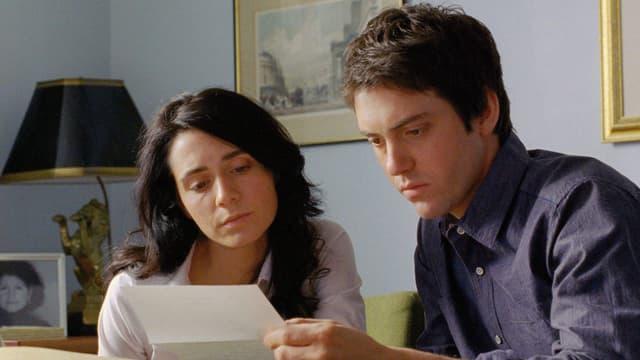 Ein Mann und eine Frau starren auf ein Blatt Papier.