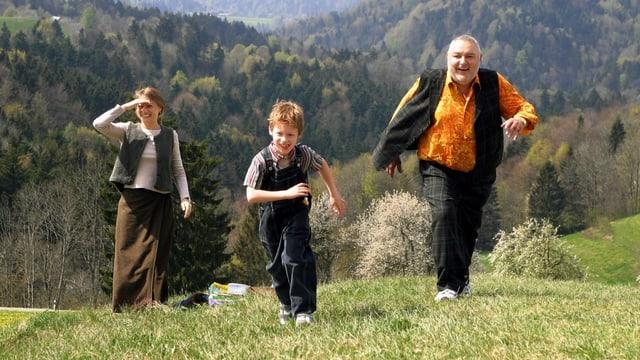 Drei Menschen gehen einen Hügel hoch.