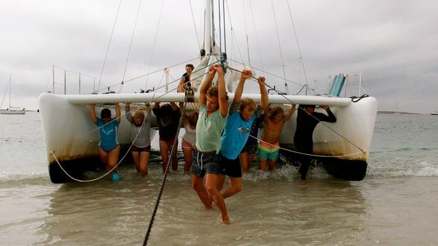 Einem Katamaran wurden die Segel eingerollt. Nun stossen es 10 Junge aus dem seichten Wasser an den Strand.