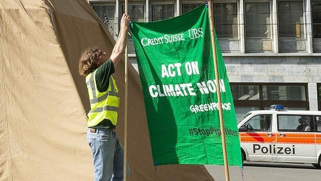 Placat da Greepeace per far attent las bancas UBS e Credit Suisse d'agir per il clima.