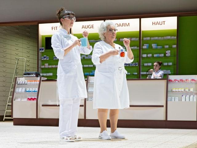 Zwei Frauen mit Apothekerkitteln trinken stehend einen Tee.