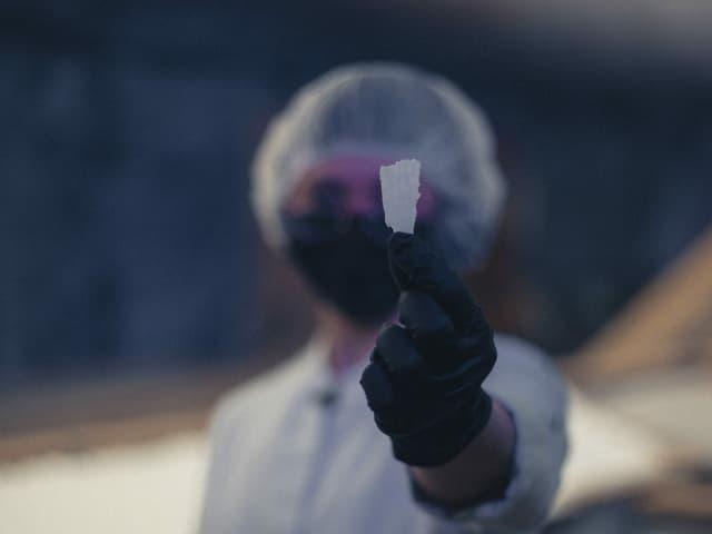 Ein Salzkristall wird in die Kamera gehalten.