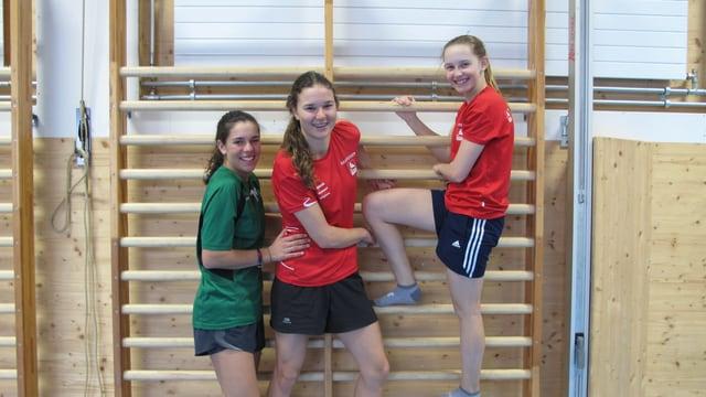 Drei Mädchen in Sportkleidung klammern sich an einer Sprossenwand fest.