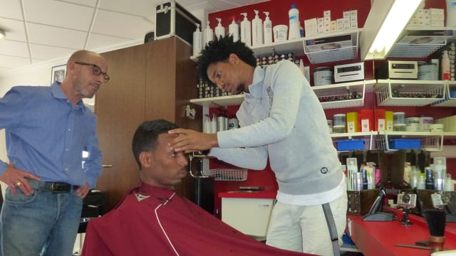 Samuel Jambo è vi da tagliar ils chavels a ses model, che sesa en ina sutga da coiffeur.