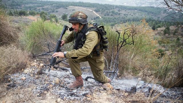 Ein Soldat inspiziert die Stelle, an der eine der Katjusha-Raketen eingeschlagen war.