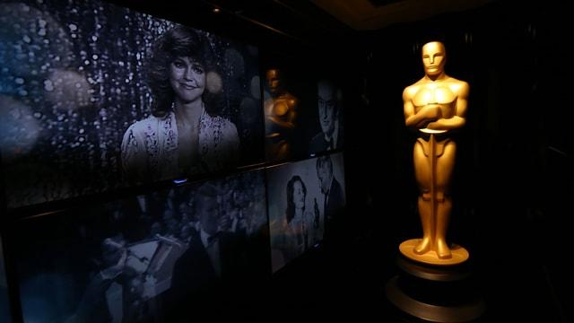Grosse Oscar-Statue in Los Angeles vor einer Leinwand mit Bildern von früheren Oscar-Verleihungen.