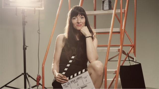 Frau in schwarzem Kleid sitzt mit Filmklappe in der Hand auf Leiter.