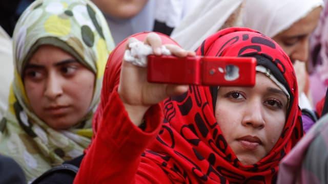 Zwei junge Frauen mit Kopftuch, die eine hält ihr Handy hoch und fotografiert