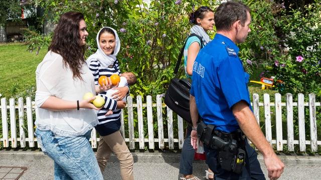 Frau mit Baby auf dem Arm läuft neben anderer Frau und hinter Polizist.