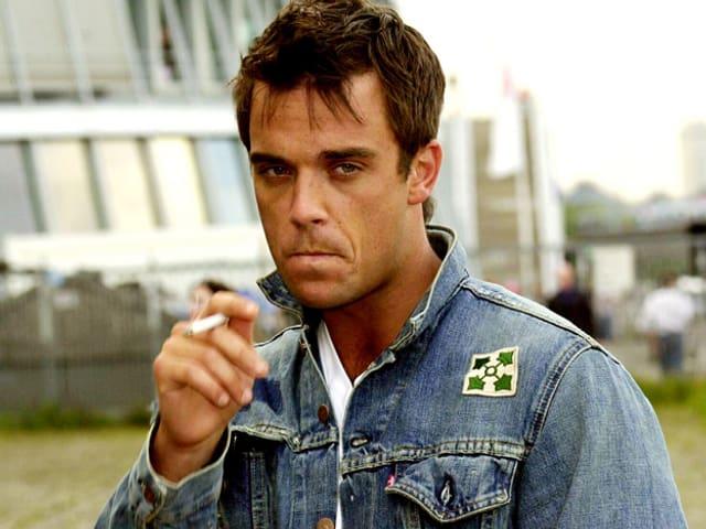 Robbie Williams in Jeansjacke, rauch eine Zigarette.