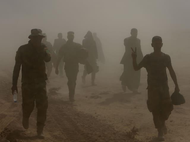 Menschen gehen auf sandigem Untergrund, wegen der staubigen Luft sind nur ihre Umrisse zu sehen.