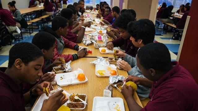 US-Schüler sitzen nebeneinander an einem Tisch und essen.