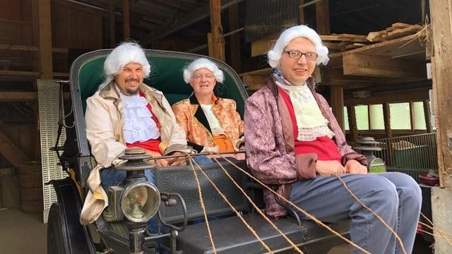 Drei Personen mit Perücken in einer Kutsche