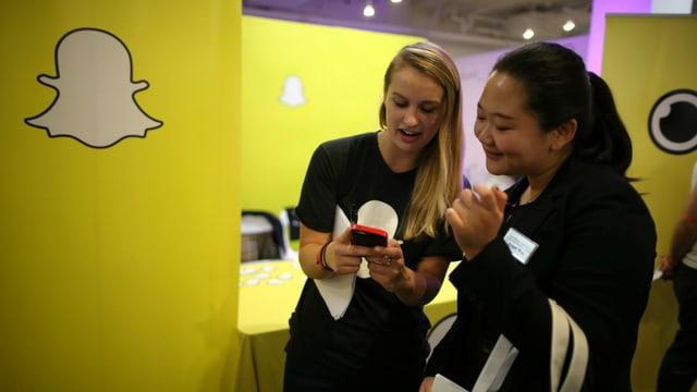 Zwei junge Frauen schauen lachend auf ein Smartphone; an der Wand das Snapchat-Logo.
