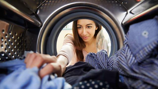 Frau räumt Waschmaschine aus.