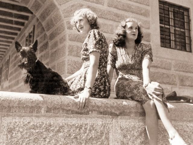 Zwei junge Frauen sitzen auf einer Mauer.