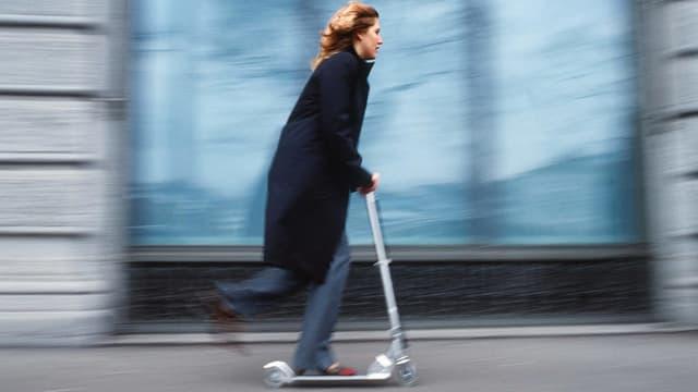 Eine Frau in Jeans und mit blauem Mantel flitzt mit einem Trottinett an einer Hausfassade vorbei.