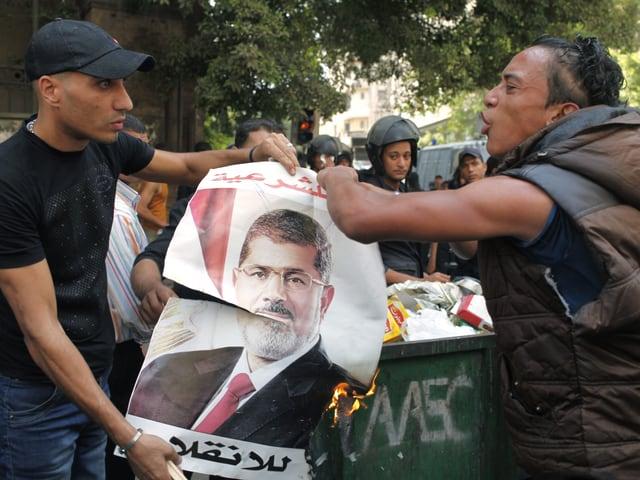 Mursi-Gegner verbrennen ein Plakat des gestürzten Präsidenten.