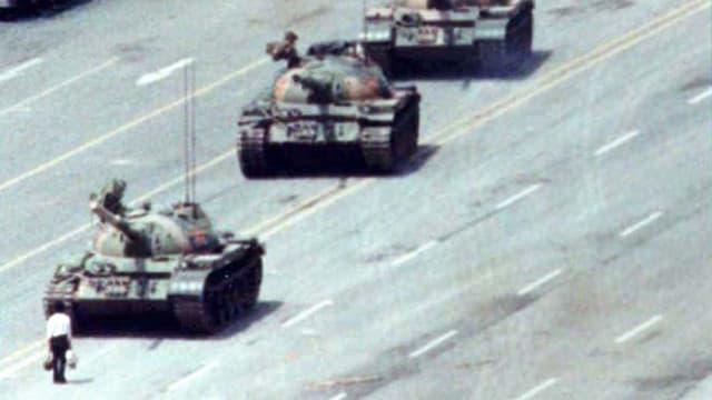 Ein Mann steht vor drei Panzern