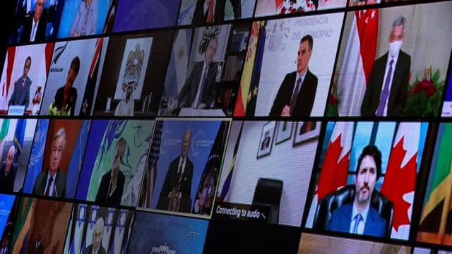 Zu sehen ein Screen mit duzenden Regierungschefinnen und -Chefs.