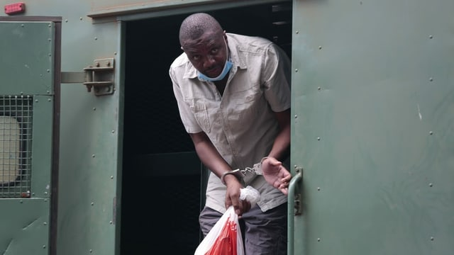 Hopewell Chin'ono verlässt den Gefangenen-Transporter in Handschellen.