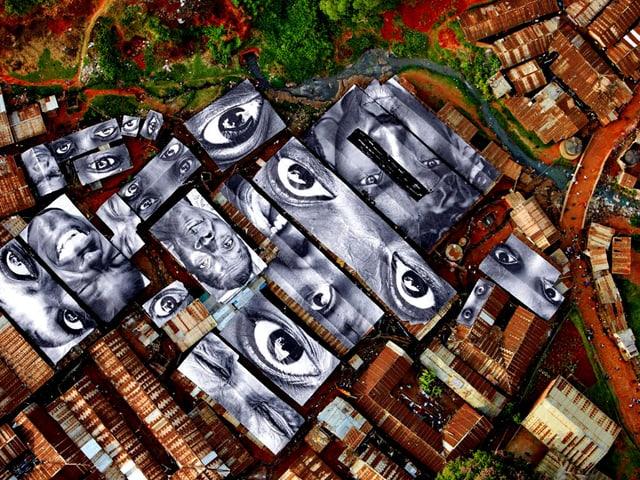 Augen und Gesichter auf Dächern von Baracken, gesehen aus der Vogelperspektive