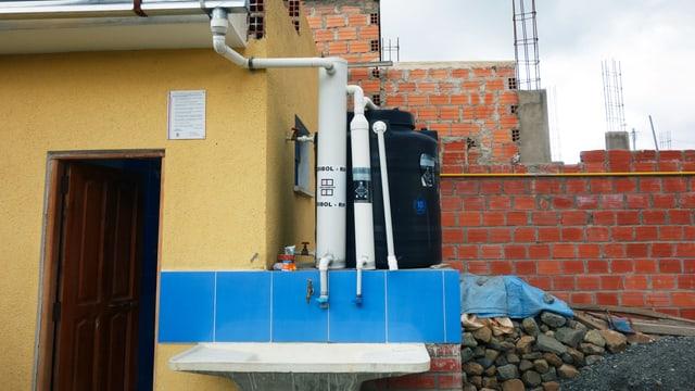 Eine Regenwasser_Auffang-Anlage mit mehreren weissen Rohren und einem Bottich.