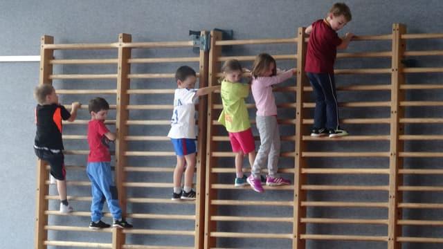 Kinder klettern an der Sprossenwand.