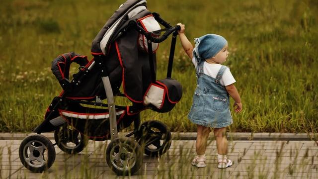 Ein kleines Kind steht allein bei einem Kinderwagen