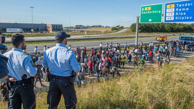 Dänische Polizisten beobachten Flüchtlinge, welche auf der Autobahn marschieren.