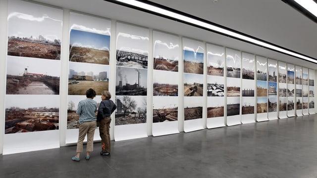 Zwei Frauen schauen sich eine Wand voller Fotografien an.