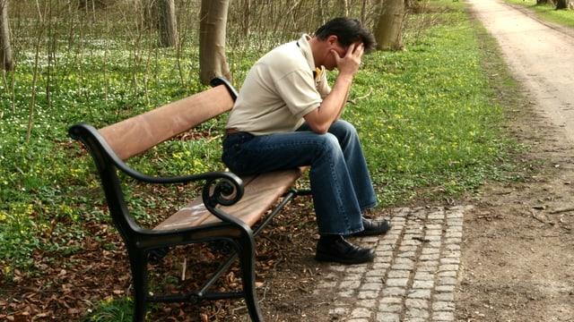 Ein Mann sitzt nachdenklich auf einer Parkbank