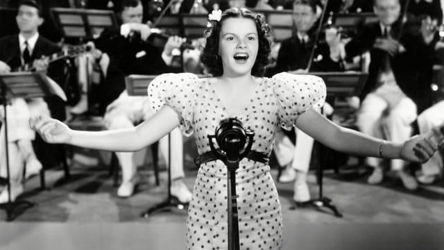Judy Garland singt. Hinter ihr das Orchester.