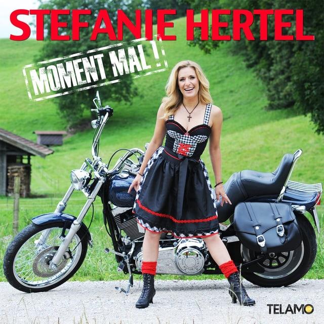 Stefan Hertel im Dirndl und vor einer Harley Davidson auf dem Cover ihres aktuellen Albums «Moment Mal!»