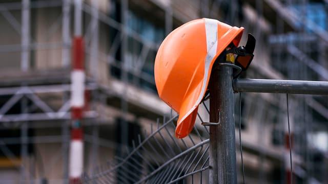 Bauarbeiter-Helm an Zaun hängend.
