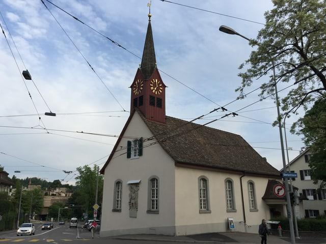 Eine Kirche, daran vorbei verläuft eine Strasse, auf der Autos fahren.