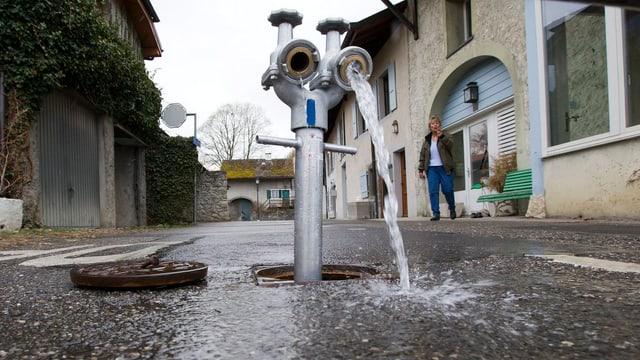 Aus einem Hydrant fliesst Wasser.