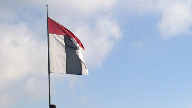 Flagge mit dem Wappen der Stadt Baden vor blauem Himmel mit Wolken.
