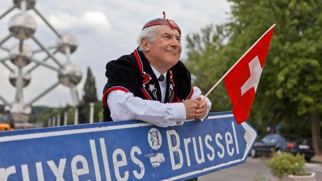 Symbolbild: Ein Mann in Apüpenzeller Tracht lehnt auf einem blauen Wegweiser, auf dem Brüssel steht, in der Hand hält er eine kleine Schweizer Fahne.