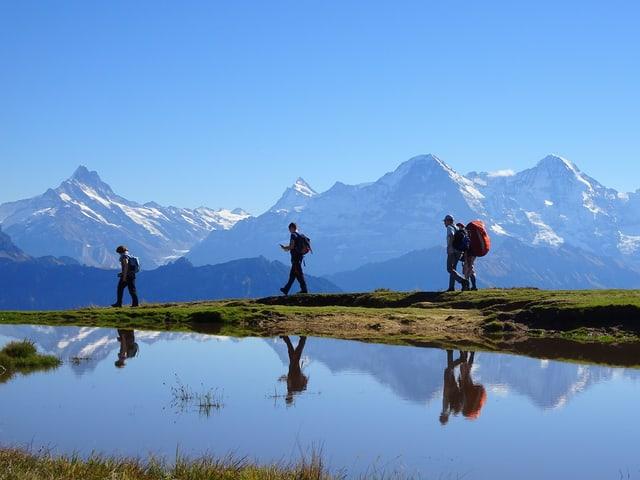 Alpen mit drei Wanderer an einem Seelein bei viel Sonnenschein.
