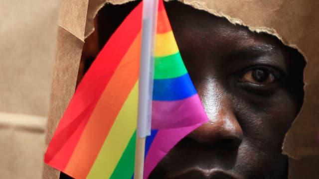 Schwuler schützt sein Gesicht mit einer Papiertüte.
