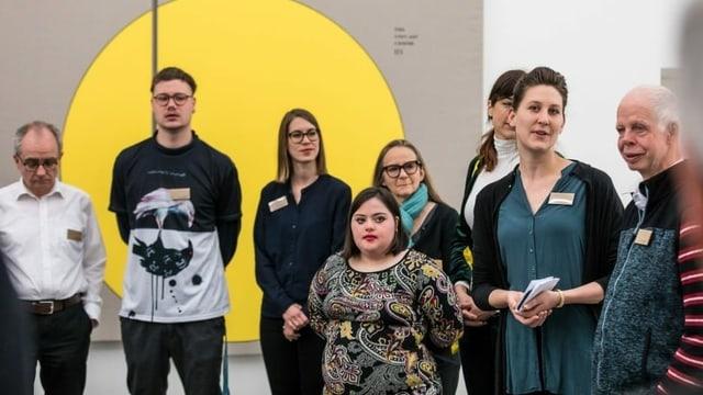 Eine Frau steht mit einer Gruppe von Menschen mit und ohne Behinderung vor einem abstrakten Gemälde.
