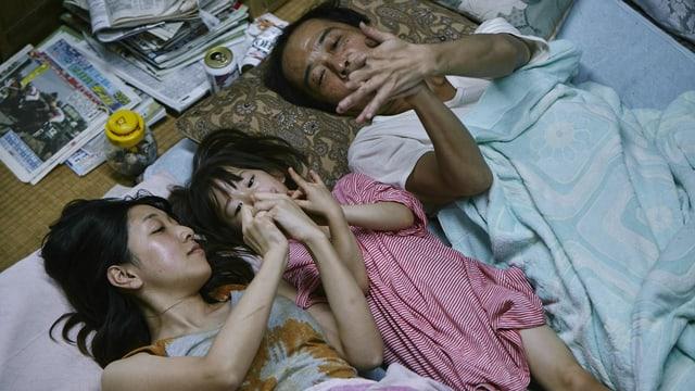 Ein Mann, eine Frau und ein Kind liegen auf Kissen am Boden und stellen mit ihren Händen Schmetterlinge dar.